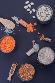 Récipients en verre plat avec différents grains. vue de dessus des tasses en verre et des mini bouteilles avec des haricots, des lentilles, du riz et du sarrasin. fond bleu foncé.