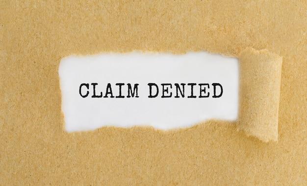 Réclamation textuelle refusée apparaissant derrière du papier brun déchiré