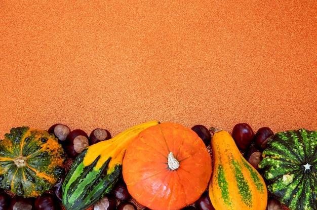 Récolte d'automne composition de citrouilles décoratives et de châtaignes sur fond orange pailleté
