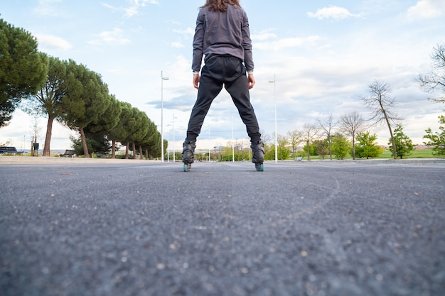 Récolte, dessous, vue postérieure, de, jeune homme, dans, sportswear, patins à roulettes, route, dans, parc ville