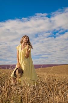 La récolte du blé mûr pousse dans le champ le grain d'or et la fille marche à travers le champ e...