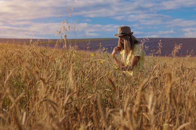 La récolte du blé mûr pousse sur le terrain le grain d'or et la fille