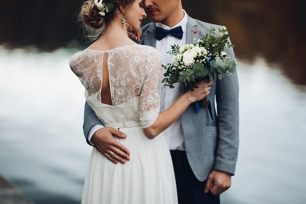 Récolte d'élégants jeunes mariés près du lac