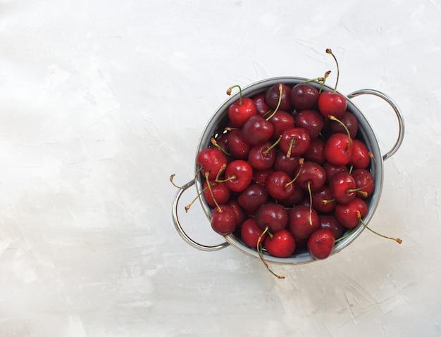 Récolte estivale, cerises fraîches dans la vue de dessus de bol en métal sur béton gris