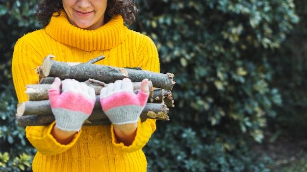 Récolte de femme tenant des tas de bois de chauffage
