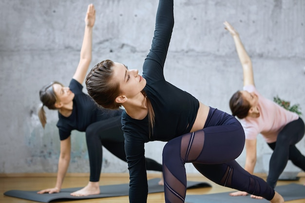 Récolte de fitnesswomen pratiquant l'étirement sur des nattes.