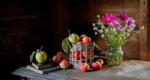 Récolte fraîche de pommes de ferme mûres et saines dans un bocal en verre, dans un panier.