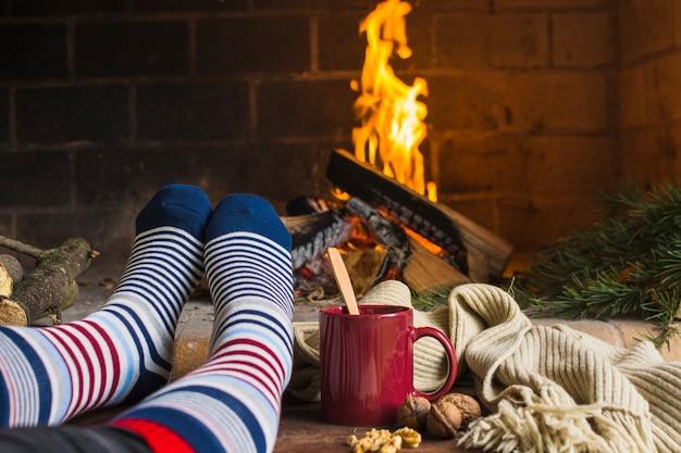 Récolte des jambes réchauffe près de la cheminée