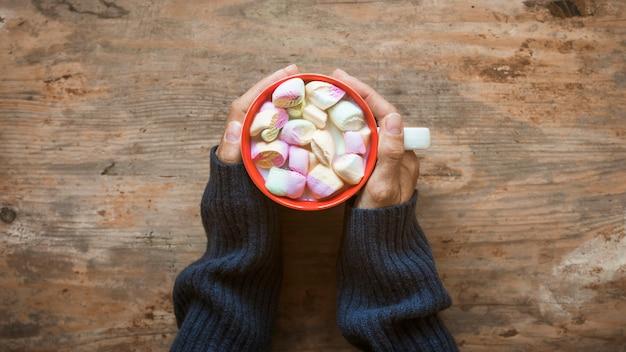 Récolte des mains réchauffant près du chocolat chaud