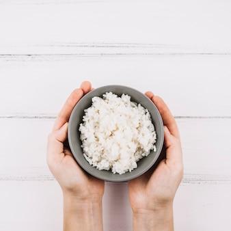 Récolte des mains tenant un bol avec du riz