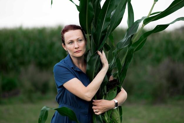 Récolte de nourriture de maïs, femme tenant la récolte sur le terrain