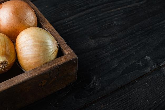 Récolte d'oignons frais, sur fond de table en bois noir avec espace de copie pour le texte