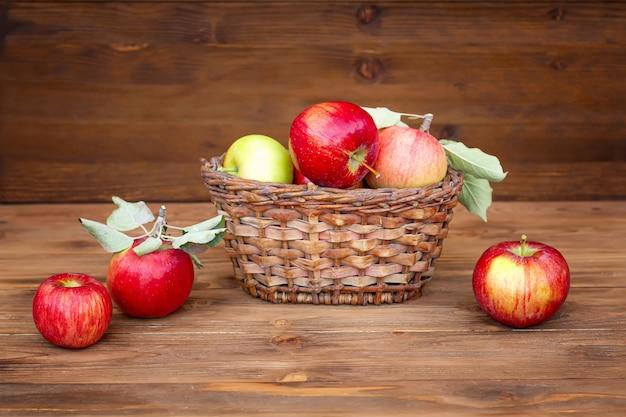 Récoltez les pommes. pommes rouges dans un panier en osier sur une vieille table en bois
