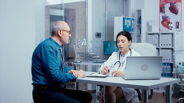 Recommandation de pilules pour patient senior du médecin dans son bureau. bilan de santé d'un hôpital ou d'une clinique privée moderne pour la prévention des maladies et les problèmes de santé. plaintes des patients et assurance-maladie