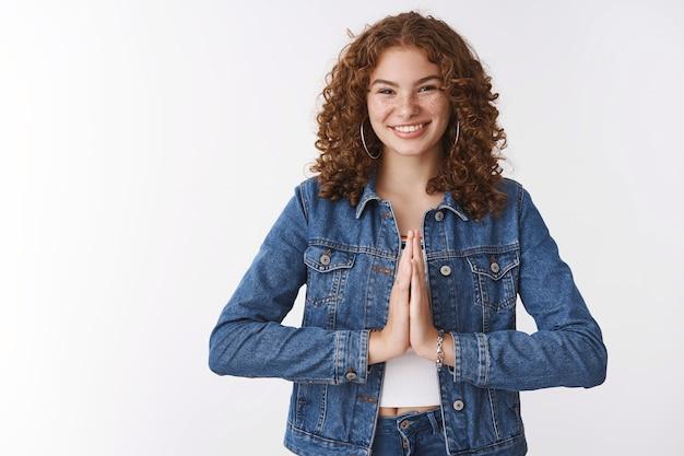 Reconnaissante jeune charmante fille rousse heureuse remerciant s'inclinant poliment presse paumes ensemble supplication prier geste souriant largement apprécier l'aide, debout fond blanc ravi