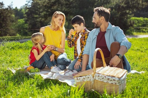 Récréatif. famille aimante exubérante, passer du temps ensemble et pique-niquer