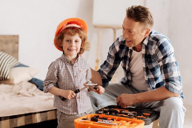 La recréation. garçon souriant aux cheveux bouclés tenant des instruments à deux mains, debout près du père tout en regardant droit à la caméra