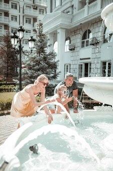 Recréer ensemble. famille souriante de touristes jouant avec l'eau de la fontaine lors de leur promenade dans la ville.