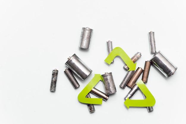 Recyclage des déchets, élimination des ordures, environnement et concept d'écologie - gros plan de piles alcalines usagées et symbole de recyclage vert