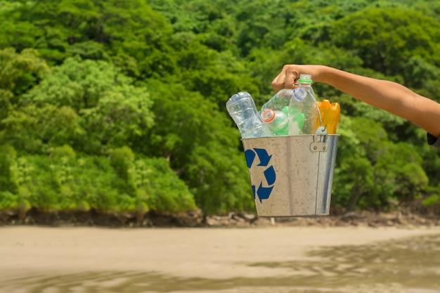 Recycler, panier avec bouteille en plastique à la plage