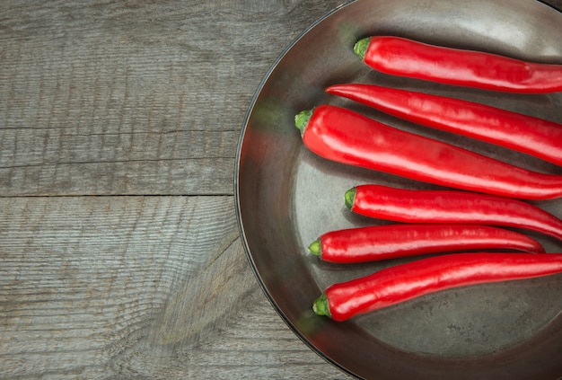 Red hot chili peppers et pan sur planche de bois vintage. vue de dessus avec espace de copie.