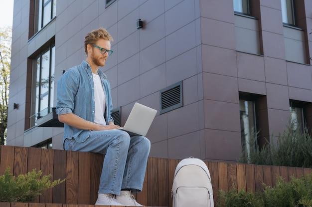 Rédacteur de l'homme à l'aide d'un ordinateur portable travaillant projet indépendant à domicile