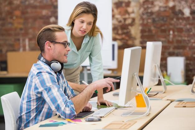 Rédacteurs photo concentrés utilisant un ordinateur dans le bureau