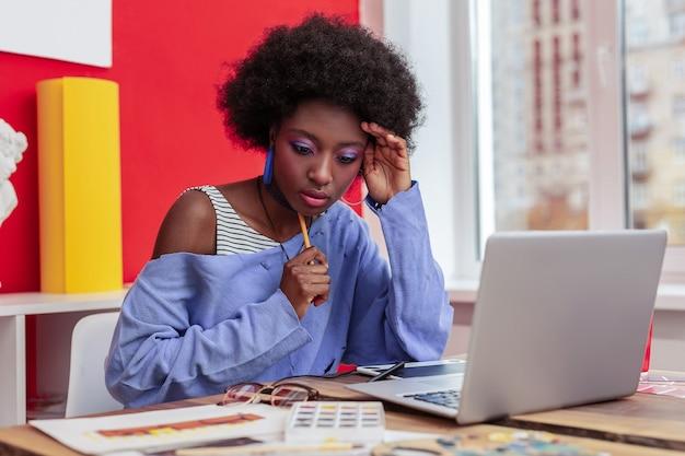 Rédaction de courrier électronique. belle étudiante internationale élégante se sentant occupée à écrire un e-mail à son professeur