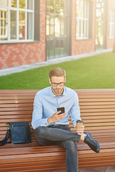 Rédaction d'un e-mail commercial d'un bel homme d'affaires utilisant un smartphone et buvant du café