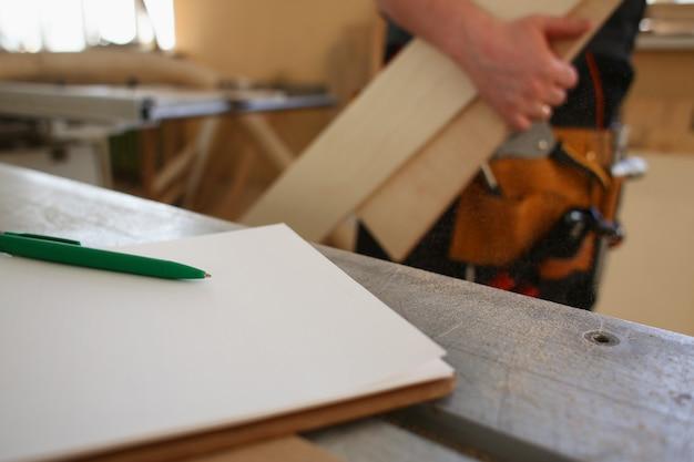 Rédaction de stylo vert couché sur le bureau sur le bloc-notes de presse-papiers agrandi.