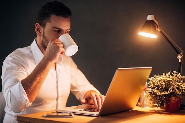 Redémarrer son énergie pour travailler plus. jeune homme confiant buvant du café