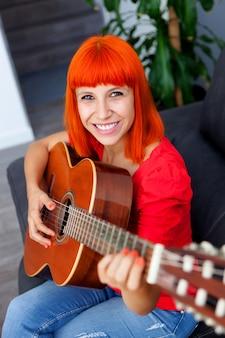 Redhaid détendue femme jouant de la guitare