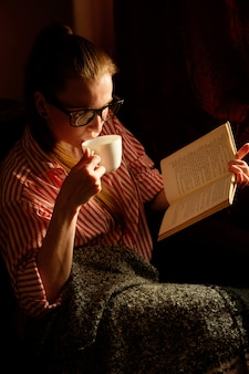 Redhead ginger girl in stripped shirt reading book, boire du café, allongé sur le canapé et souriant