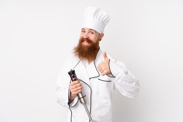 Redhead man using hand blender over white wall donnant un coup de pouce vers le haut