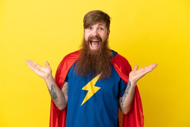 Redhead super hero homme isolé sur fond jaune avec une expression faciale choquée