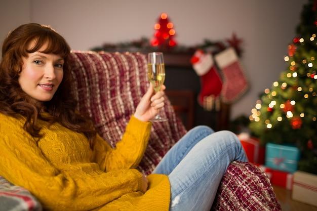 Redhead tenant un verre de champagne sur un canapé à noël