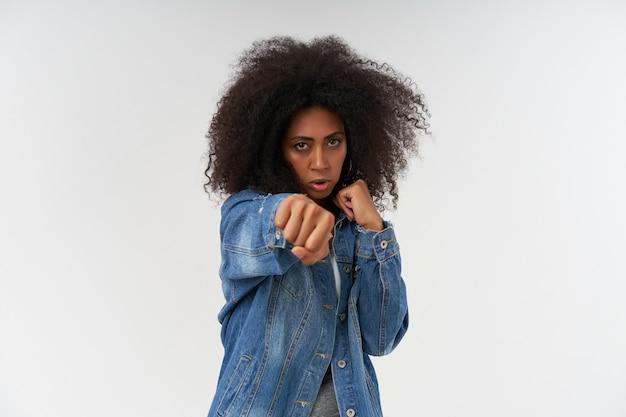 Redoutable boxe femme à la peau foncée bouclée avec les poings levés en haut blanc et manteau en jean, debout sur un mur blanc et intimidant