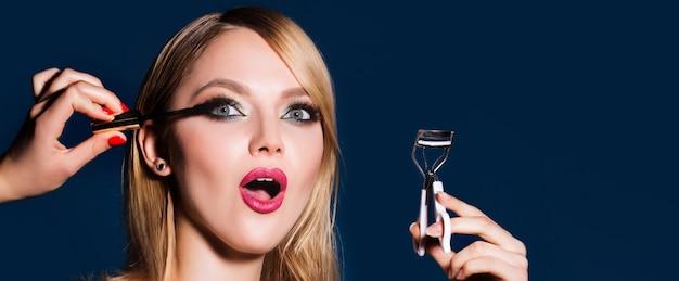 Redresseur de cils. la maquilleuse applique du mascara sur les cils. femme faisant son maquillage à l'aide de mascara noir se brossant les cils. maquillage des lèvres rouge vif, peau parfaitement propre, ombres à paupières.