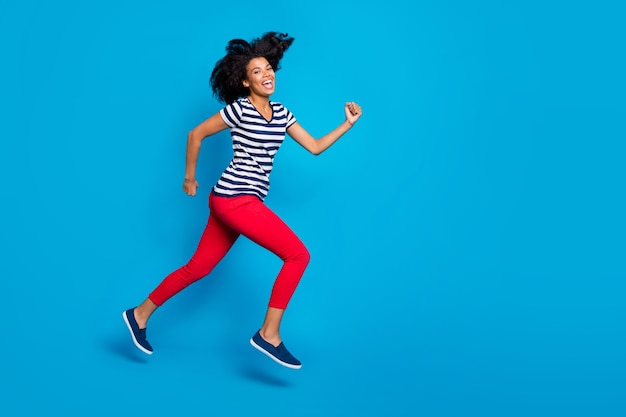 Réductions je ici! photo de côté de profil pleine taille de folle brune funky cheveux bouclés mulâtre fille sauter courir les bonnes affaires vendredi noir sentir les émotions de contenu porter tenue décontractée fond de couleur bleu isolé