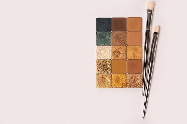 Refils d'ombres à paupières de couleurs dorées et brunes avec des pinceaux de maquillage sur fond blanc. espace pour le texte