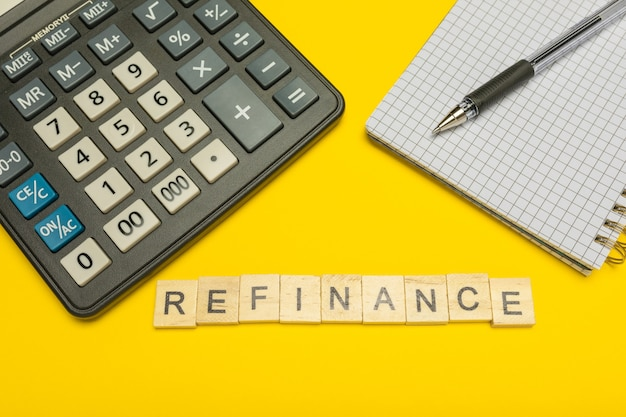 Le refinancement de mot fait avec des lettres en bois sur une calculatrice jaune et moderne avec un stylo et un cahier.