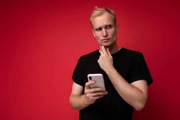 Réfléchi beau jeune homme isolé sur le mur de fond portant des vêtements de tous les jours tenant et utilisant un téléphone mobile écrivant des sms regardant sur le côté et en pensant.