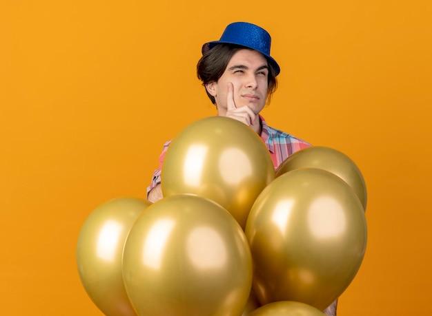 Réfléchi bel homme caucasien portant chapeau de fête bleu se dresse avec des ballons d'hélium