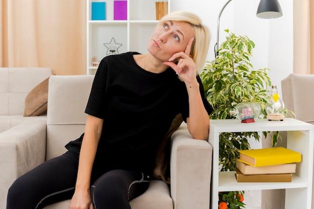 Réfléchi belle blonde femme russe est assise sur un fauteuil mettant la main sur le temple en levant