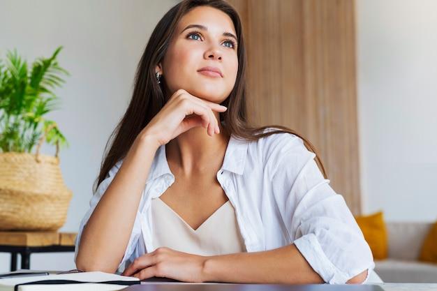 Réfléchi belle femme brune en chemise blanche, sourit, pense à des choses agréables.