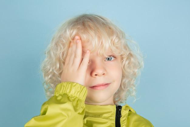 Réfléchi. bouchent le portrait du beau petit garçon caucasien isolé sur le mur bleu. modèle masculin blond bouclé. concept d'expression faciale, émotions humaines, enfance,