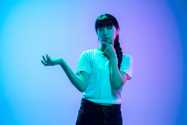 Réfléchi, choisissant. portrait de jeune femme asiatique sur fond de studio dégradé bleu-violet à la lumière du néon. concept de jeunesse, émotions humaines, expression faciale, ventes, publicité. beau modèle brune.