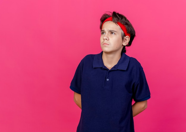Réfléchi jeune beau garçon sportif portant un bandeau et des bracelets avec des appareils dentaires en gardant les mains derrière le dos en regardant à côté isolé sur fond cramoisi avec espace de copie
