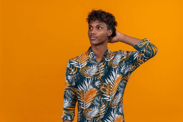 Réfléchi jeune bel homme à la peau sombre avec des cheveux bouclés en chemise imprimée de feuilles en gardant la main sur la tête en pensant sur un fond orange