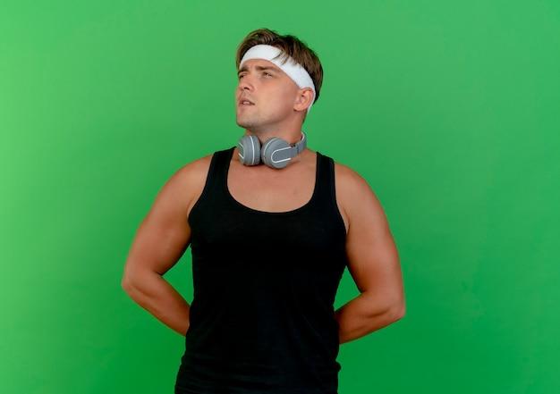 Réfléchi jeune bel homme sportif portant un bandeau et des bracelets avec des écouteurs sur le cou mettant les mains derrière le dos à côté isolé sur mur vert